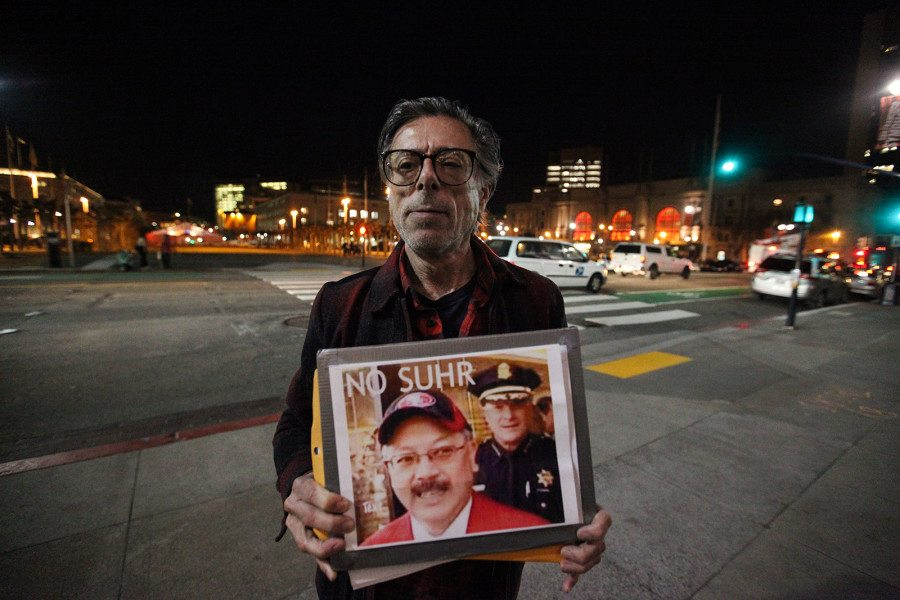 Curt Wechsler holds sign outside of San Francisco City Hall on Wednesday night during the Police Commission's meeting about use of force. (Ekevara Kitpowsong/ Special to S.F. Examiner)