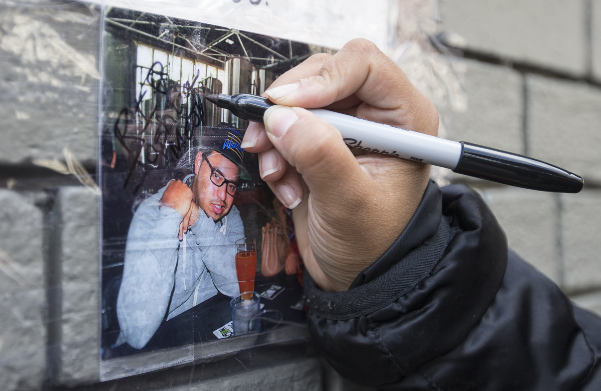 Marlene DeLeon writes a message on a memorial for her husband, Joshua Mejia, on Geary Street Monday, July 19, 2016. Meija was shot and killed near Geary and Post streets in the early hours of Sunday, July 18, 2016 in San Francisco, Calif. (Jessica Christian/S.F. Examiner)