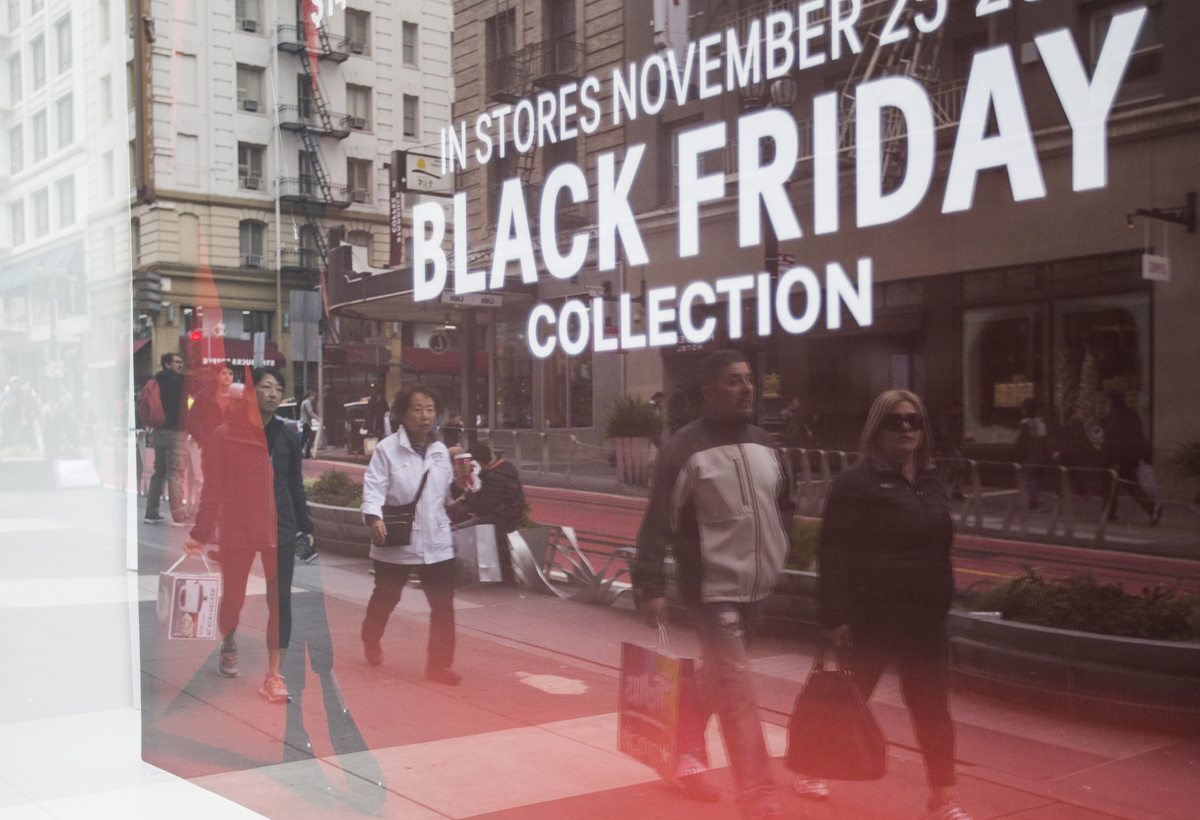 Black Friday shoppers are seen reflected in a window as they move down Powell Street in San Francisco's Union Square Friday, November 25, 2016. (Jessica Christian/S.F. Examiner)