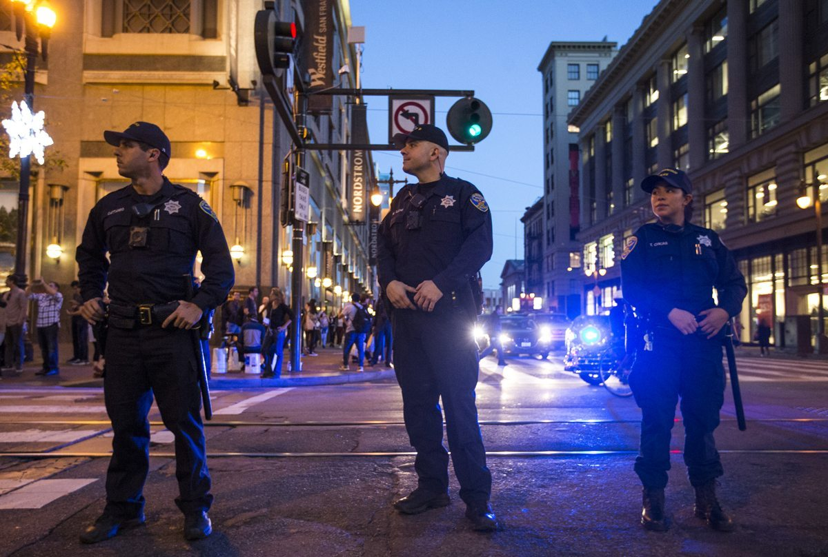 SFPD officers line Market Street as demonstrators move toward the Castro District in San Francsico, Calif. Wednesday, November 9, 2016 protesting the electoral vote of Donald Trump for President-elect. (Jessica Christian/S.F. Examiner)