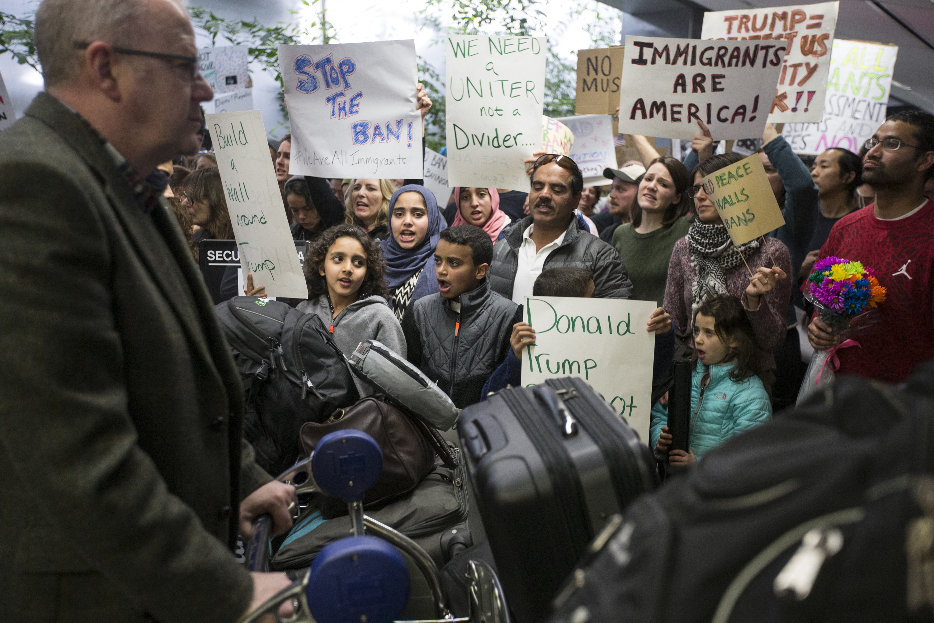 People gather near the exit of customs screening during a protest held at San Franicsco International Airport in San Francisco, Calif. Sunday, January 29, 2017. (Jessica Christian/S.F. Examiner)