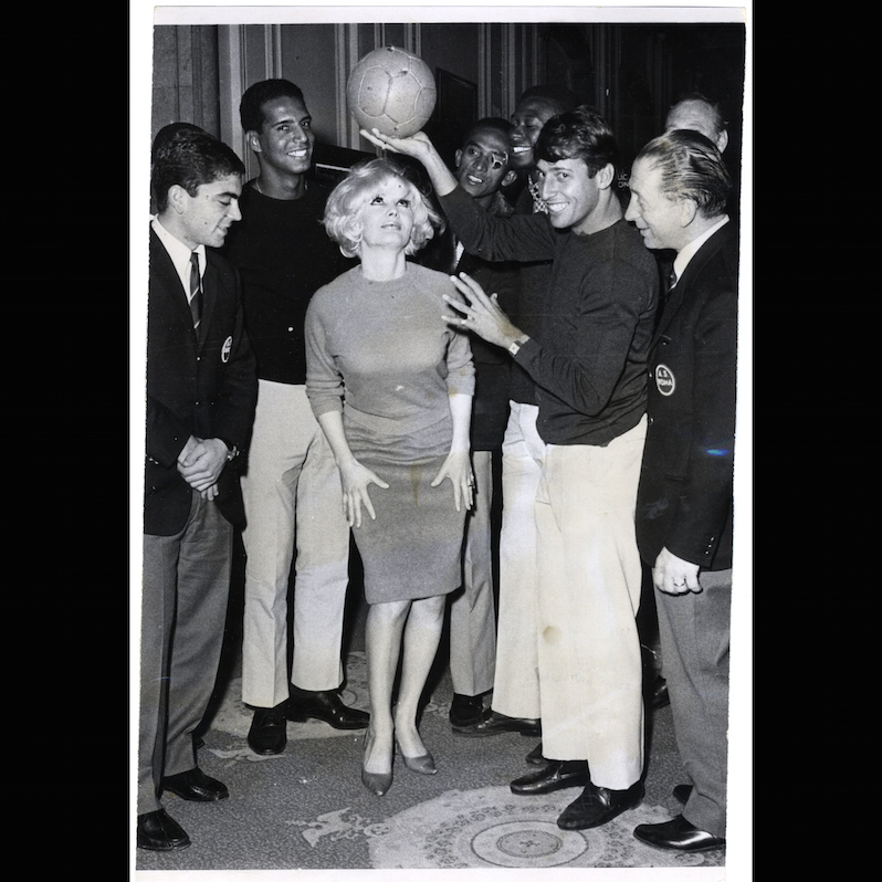 Carol Doda displays her talents with visiting Brazilian and Italian soccer players, 1967, S.F. Examiner