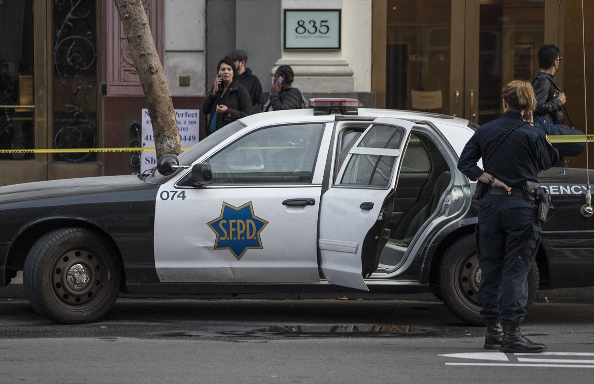 Officers investigate after someone set fire to the back seat of an SFPD vehicle near Fourth and Market streets in San Francisco, Calif. Tuesday, November 15, 2016. (Dan Chambers/Special to S.F. Examiner)