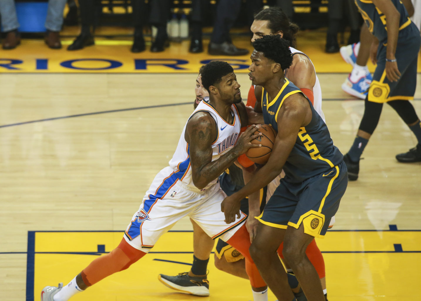 Forward Damion Jones (15) of the Golden State Warriors tries to block the path of Paul George (13) of the Oklahoma City Thunder during the first quarter of the game on November 21, 2018 at Oracle Arena in Oakland, California. (Chris Victorio - Special to S.F. Examiner)