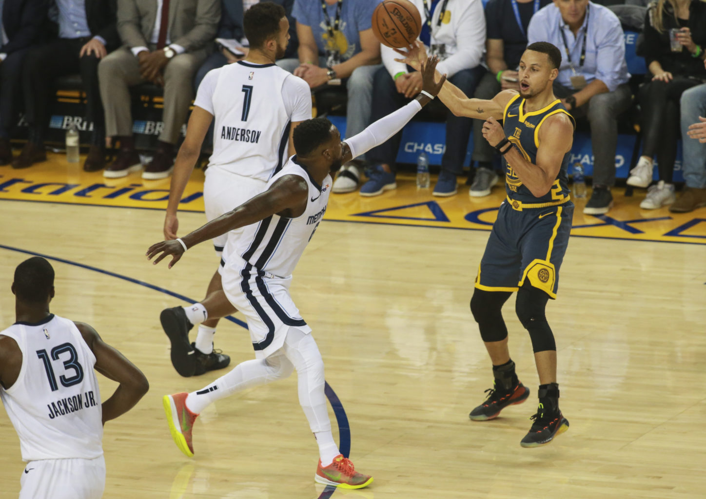 Stephen Curry (30) of the Golden State Warriors passes the ball around before Shelving Mack (6) of the Memphis Grizzlies tries to get block the play during first quarter of the game on December 17, 2018 at Oracle Arena in Oakland, California. (Chris Victorio