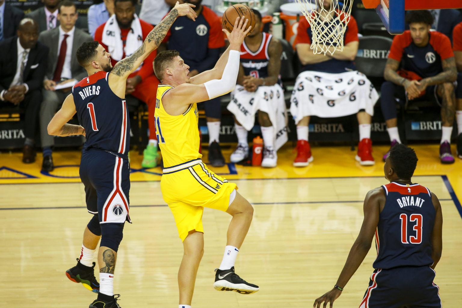 OAKLAND, CA - OCT 24: Forward Jonas Jerebko #21 of the Golden State Warriors drives towards the basket for a score past Austin Rivers #1 of the Washington Wizards during the fourth quarter of the game on October 24, 2018 at Oracle Arena in Oakland, California. (Chris Victorio / Special to S.F. Examiner)