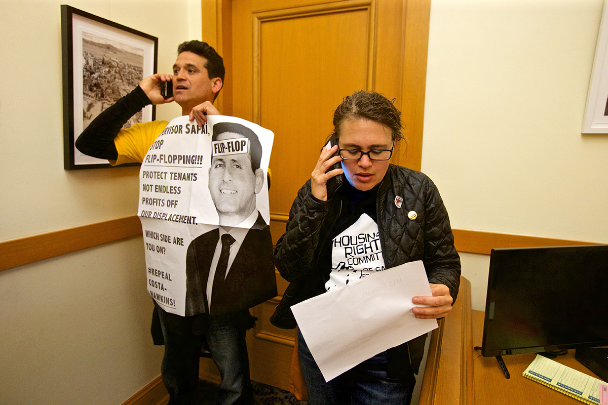 """Gilbert Williams, left, with the Alliance of Californians for Community Empowerment Action, and Sarah """"Fred"""" Sherburn-Zimmer, executive director of the Housing Rights Committee of San Francisco, speak with District 11 tenants on the phone in Supervisor Ahsha Safai's office as tenants rights advocates stage a protest to call Safai out for """"flip-flopping"""" on Proposition 10 at City Hall on Monday, Sept. 17, 2018. (Kevin N. Hume/S.F. Examiner)"""