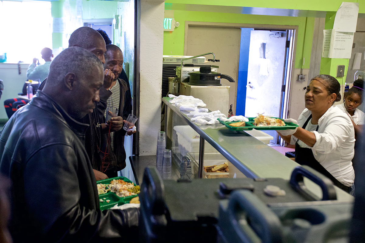 Food server Elizabeth Salmons hands out trays of tuna casserole at Mother Brown's Dining Room United Council of Human Services in the Bayview District on Wednesday, Sept. 5, 2018. (Kevin N. Hume/S.F. Examiner)