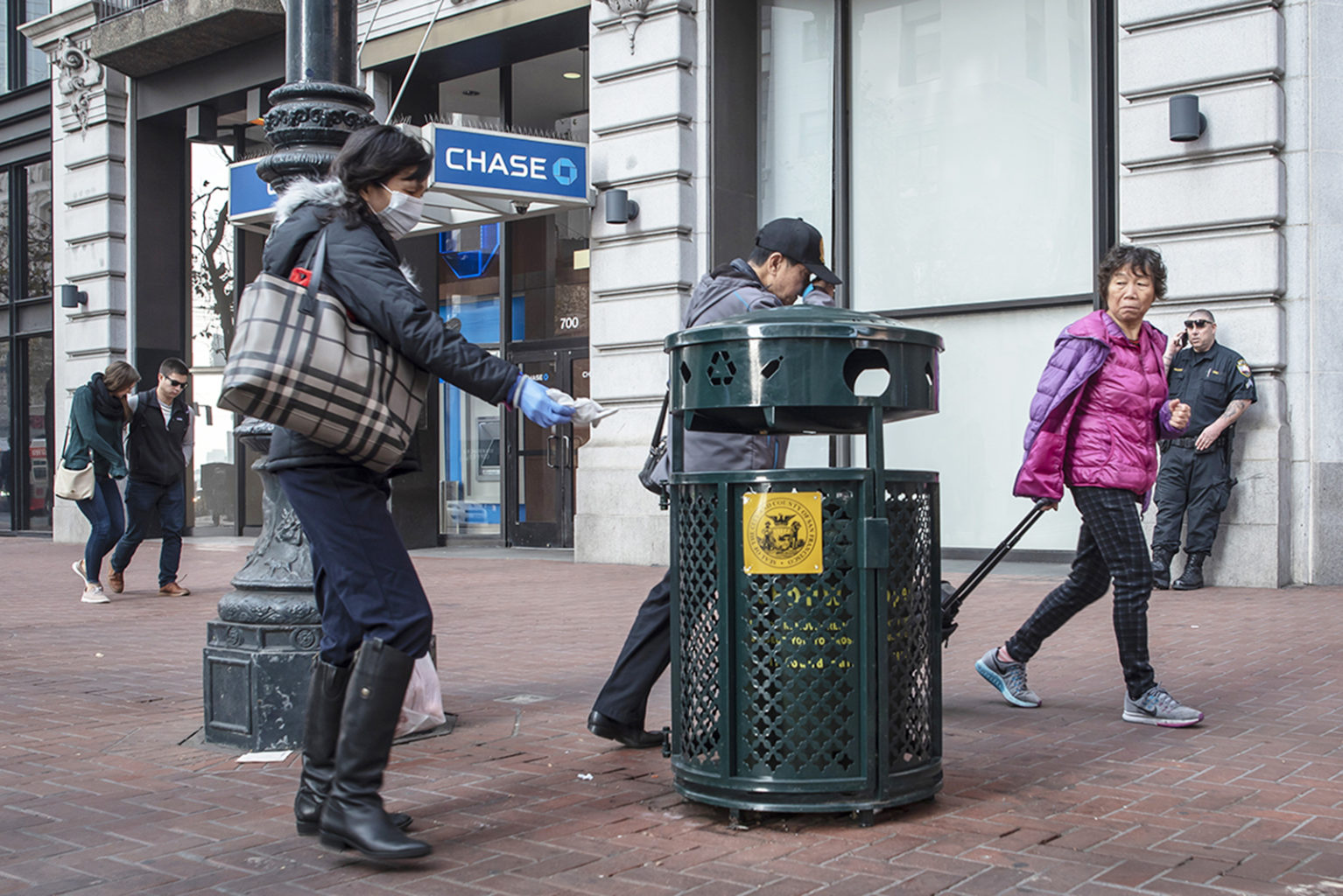 A woman throws an item away in a trash can on Market Street on Tuesday, Nov. 20, 2018. (DavÌd RodrÌguez/Special to S.F. Examiner)