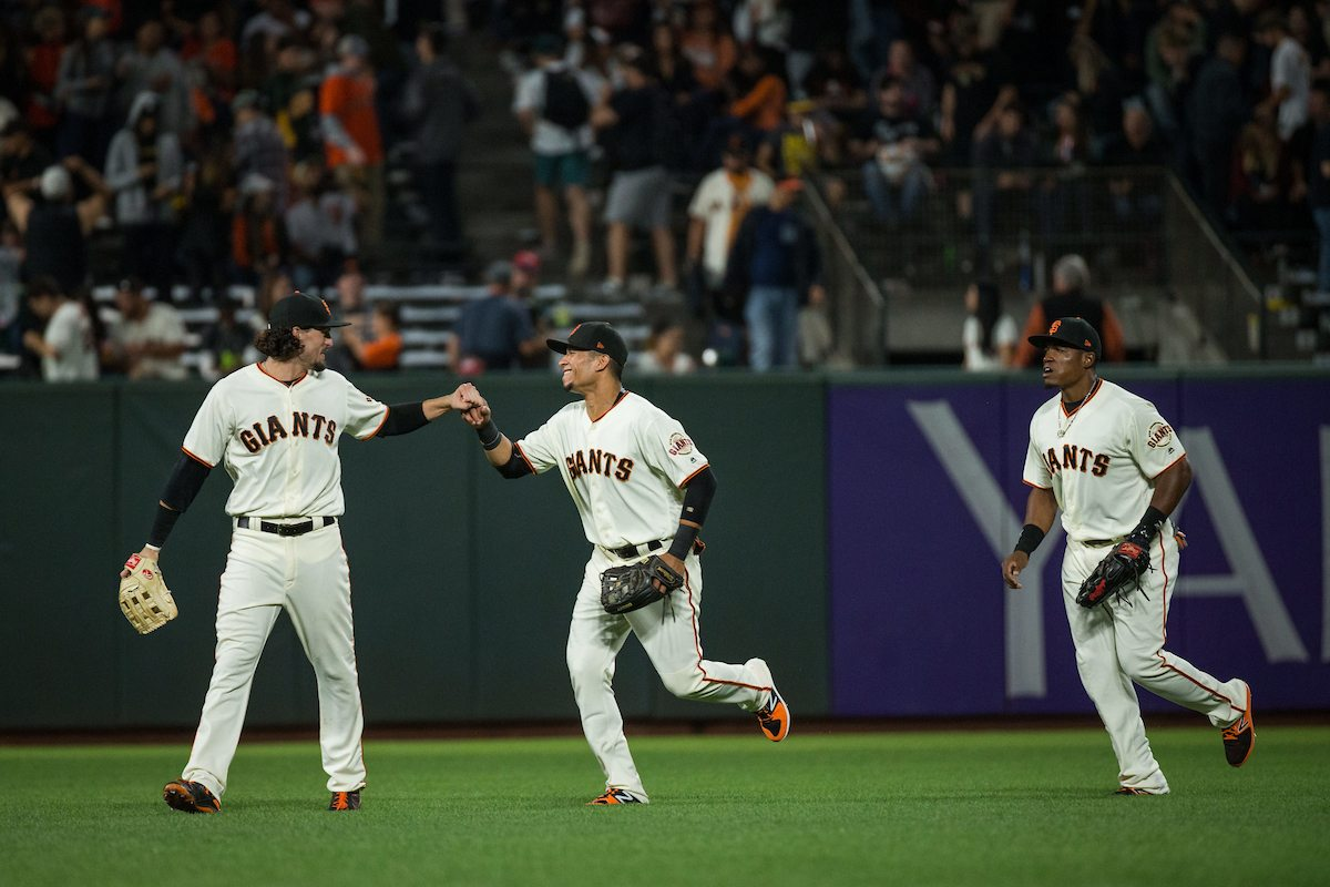 The outfield bump fists after defeating the Oakland Athletics 11-2 at AT&T Park in San Francisco, California, on August 3, 2017. (Stan Olszewski/Special to S.F. Examiner)