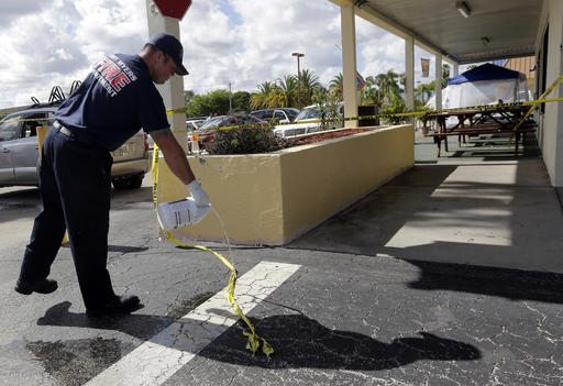 A Fort Myers fire fighter pours bleach over blood stains on the pavement at the scene of a deadly shooting outside the Club Blu nightclub in Fort Myers, Fla., on Monday. (AP Photo/Lynne Sladky)