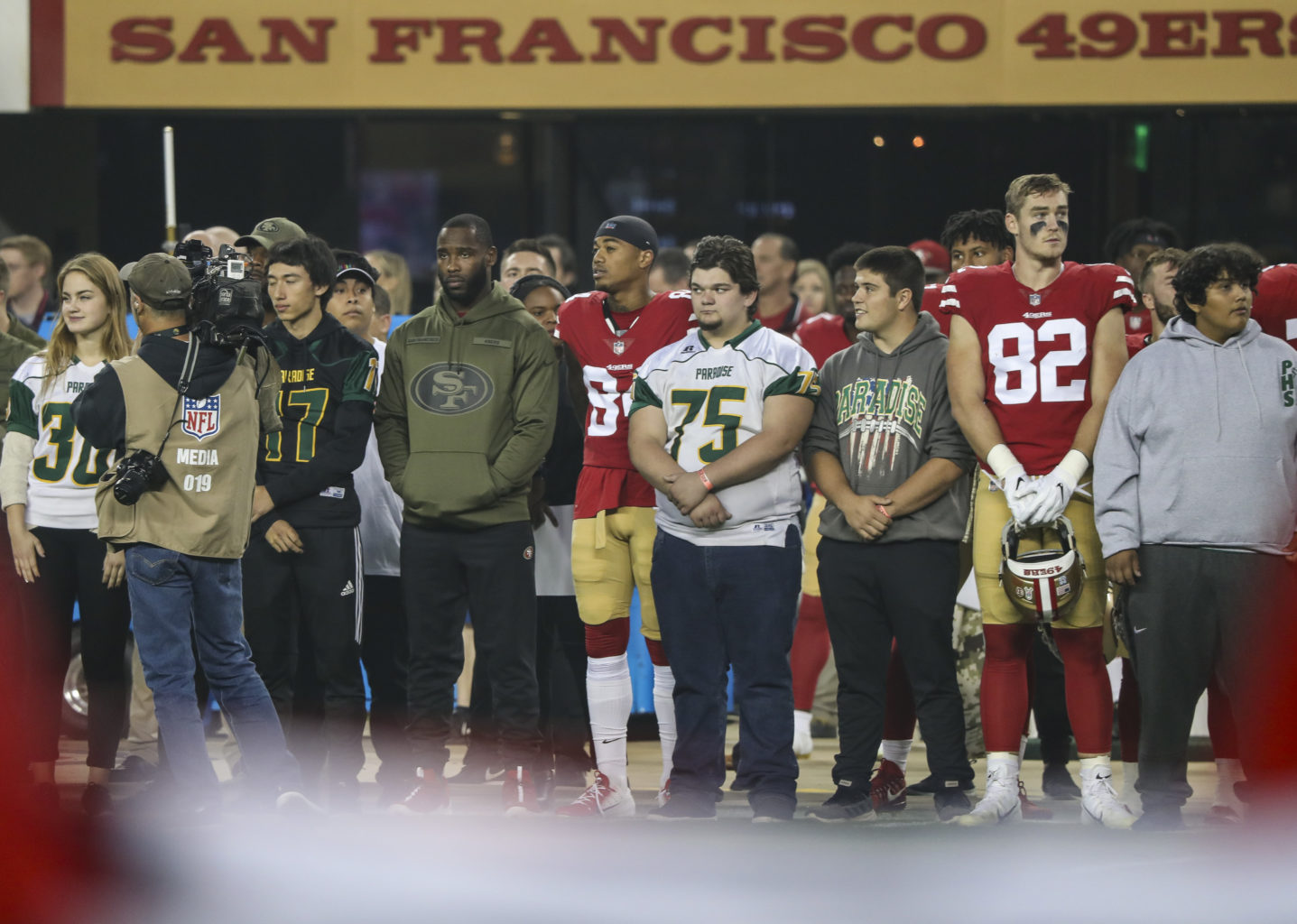 Members of the Paradise City High School student body join the San Francisco 49ers team bench during singing of the Nation Anthem before the NFL football game between the New York Giants and the San Francisco 49ers at Levi's Stadium on November 12, 2018 in Santa Clara, California. (Chris Victorio / Special to S.F. Examiner).