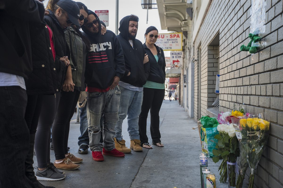 Friends and family gather to set up a memorial for Joshua Mejia on Geary Street Monday, July 19, 2016. Meija was shot and killed near Geary and Post streets in the early hours of Sunday, July 18, 2016 in San Francisco, Calif. (Jessica Christian/S.F. Examiner)