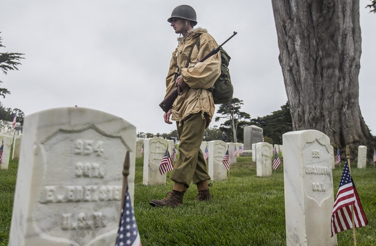 A World War II reenactor walks through graves during the 149th annual Memorial Day Ceremony at the San Francisco National Cemetery in San Francisco's Presidio Monday, May 29, 2017. (Jessica Christian/S.F. Examiner)
