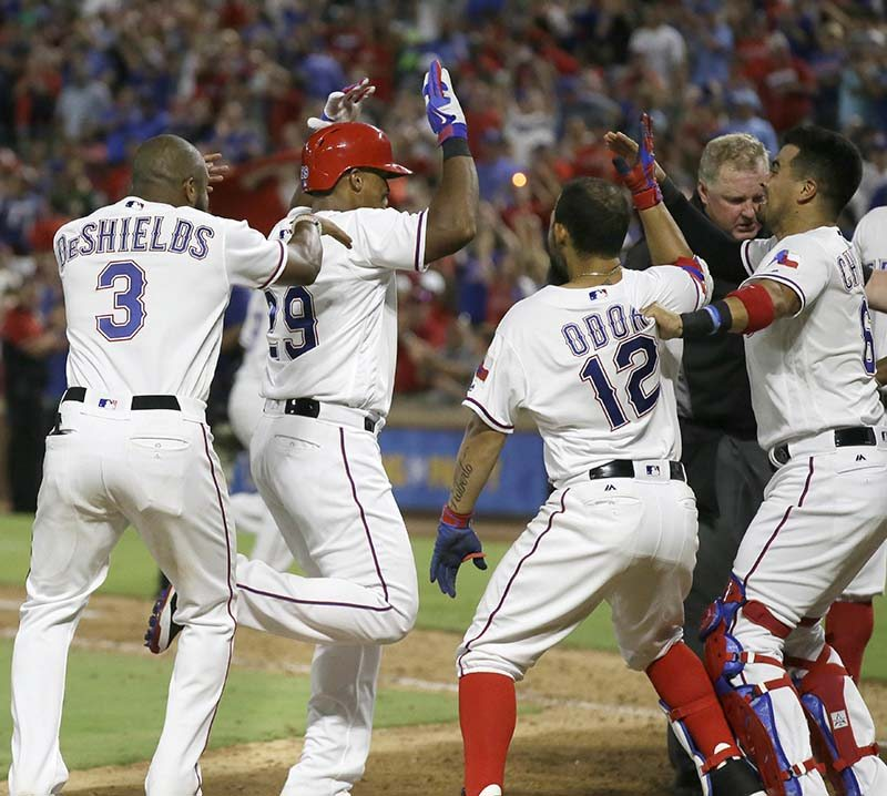 Texas Rangers Adrian Beltre (29) is met at home plate by teammates Delino DeShields (3), Rougned Odor (12) and Robinson Chirinos (61) after Betre's game winning two-run homer during the ninth inning of a baseball game against the Oakland Athletics in Arlington, Texas, Monday, July 25, 2016. The Rangers won 7-6. (LM Otero/AP)