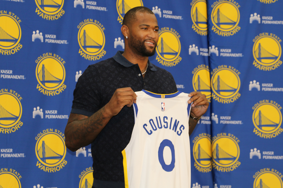 DeMarcus Cousins holds up his Golden State Warriors jersey during his introductory press conference on July 19, 2018. (Ryan Gorcey / S.F. Examiner)