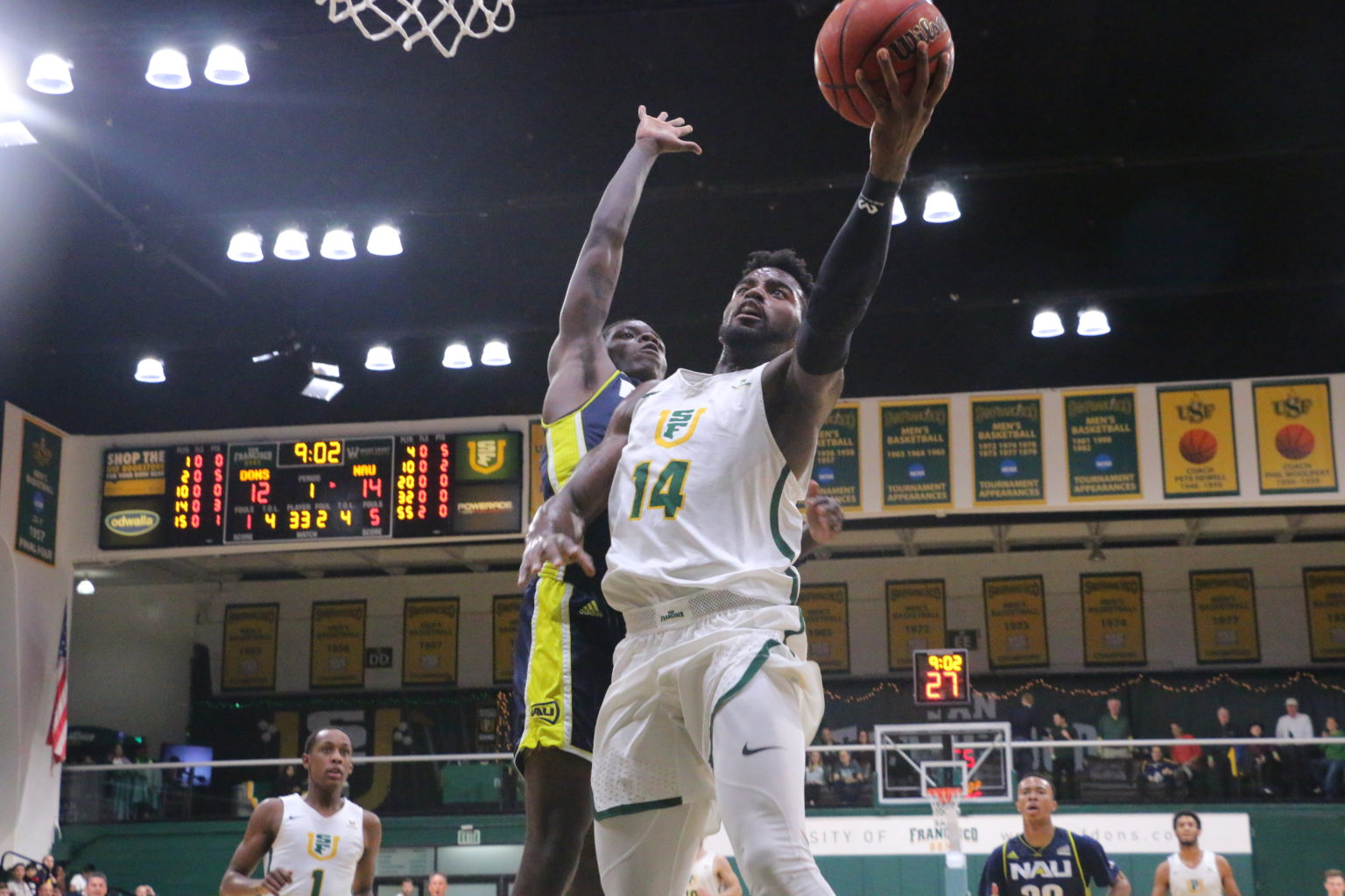 University of San Francisco guard Charles Minlend (14) goes up for a layup in the first half of a game against Northern Arizona on Dec. 19, 2018, at War Memorial Gymnasium in the Sobrato Center in San Francisco, Calif. Minlend finished with 18 points. (Ryan Gorcey / S.F. Examiner)