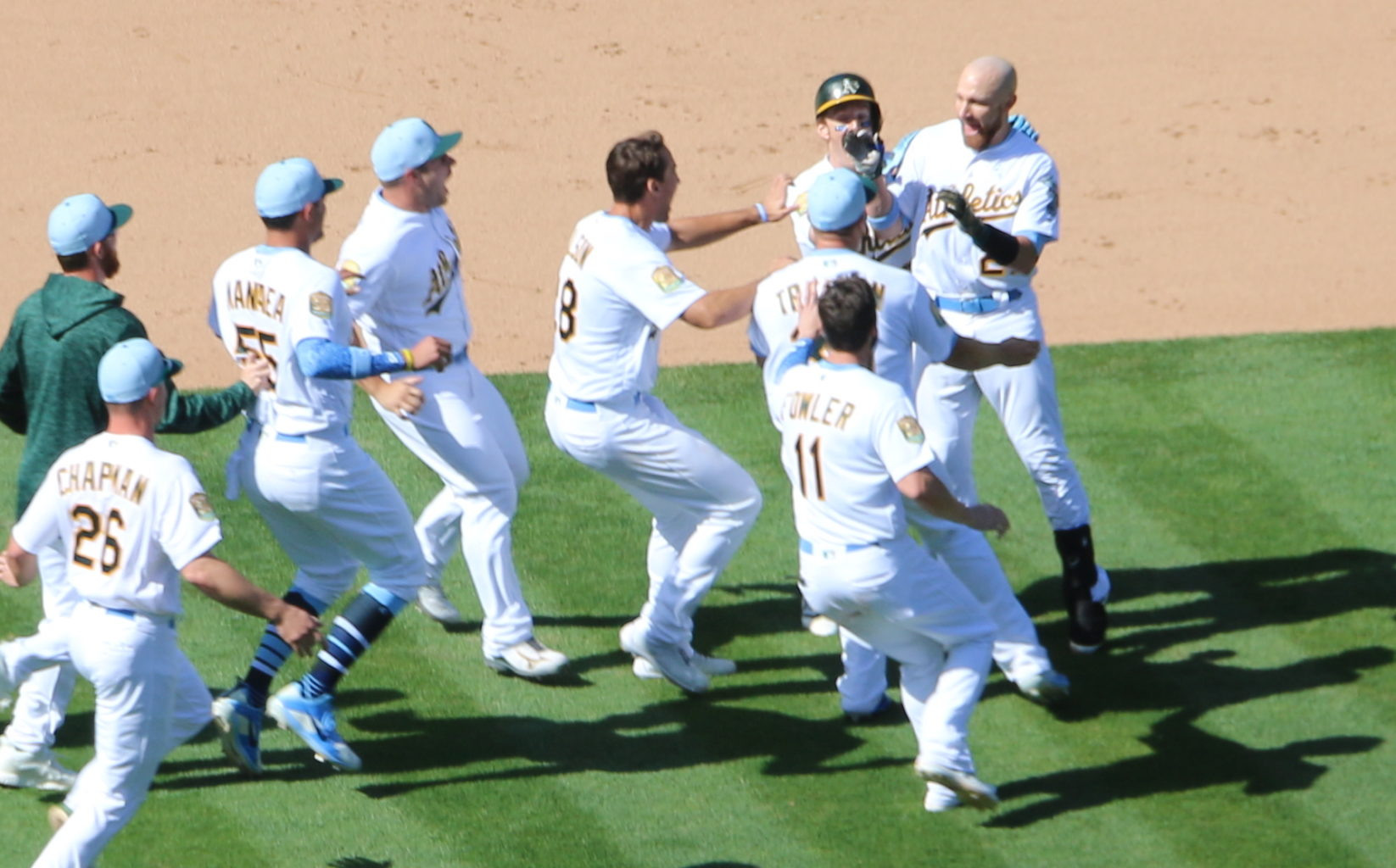 Jonathan Lucroy (right) celebrates with his teammates after his sixth career walk-off hit. (Ryan Gorcey / S.F. Examiner)