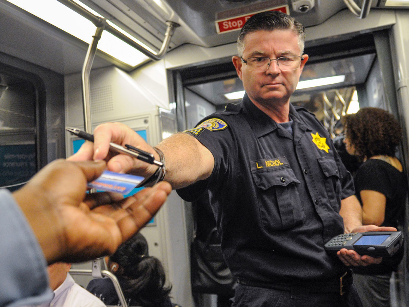 SFMTA fare evasion supervisor Lawrence Nichol checks proof of payment on a train. (Jessica Christian/2014 S.F. Examiner)