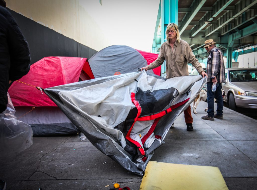 """A 40-year-old homeless man """"Polar Bear"""" takes down his tent in preparing to move to Pier 80 homeless shelter while two staffs members from San Francisco Homeless Outreach Team wait to escort him to their car on Division Street in San Francisco, Calif. Thursday, February 25, 2016.  (Ekevara Kitpowsong/ Special to S.F. Examiner)"""