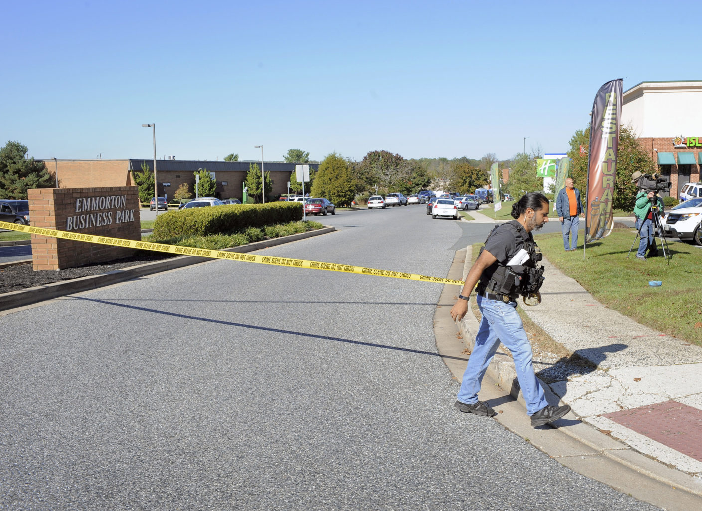A police officer puts up crime scene tape at the scene of shooting at Emmorton Business Park, the scene of a workplace shooting where five people were shot and three are confirmed dead Wednesday, Oct. 18, 2017 in Edgewood, Md. The shooting was at the Advanced Granite Solutions inside Emmorton Business Park. (Kenneth K. Lam/Baltimore Sun/TNS)