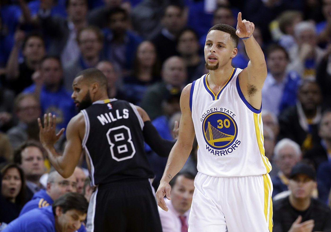 Warriors' Stephen Curry signals to his team in front of Spurs' Patty Mills (8) during the game Monday. (AP Photo/Marcio Jose Sanchez)