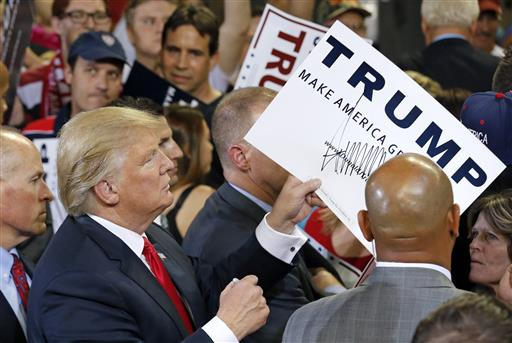 Republican presidential candidate Donald Trump signs autographs after speaking at a rally Saturday in Phoenix. (AP Photo/Ross D. Franklin)