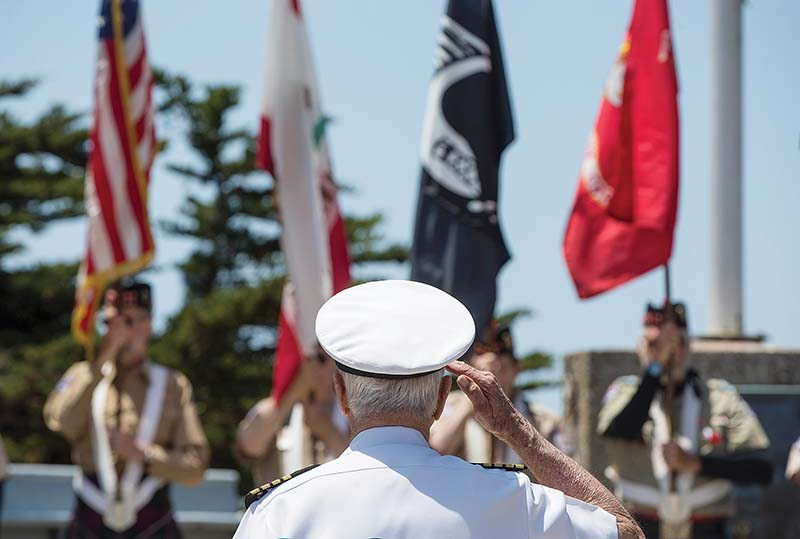 U.S. Navy Capt. Stanley E. Ellexson Jr. salutes as the colors are retired during the USS San Francisco WWII Memorial Ceremony at Fort Miley on Sunday. (Jessica Christian/S.F. Examiner)