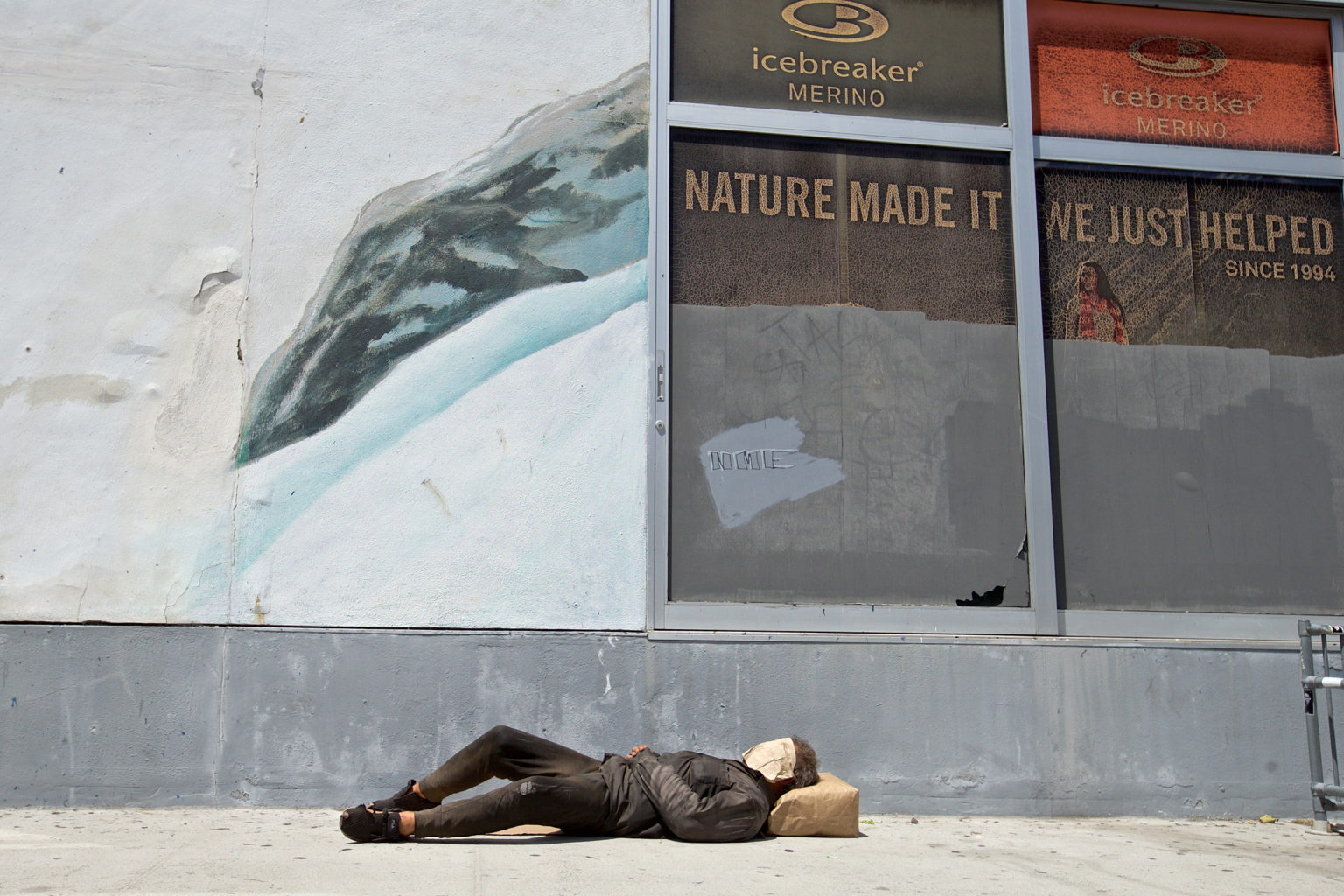 A homeless man sleeps on the sidewalk outside the old Lombardi Sports building on Polk Street on May 16. One of many community benefit districts in The City is along a stretch of Polk between California and Broadway. (Kevin N. Hume/S.F. Examiner)