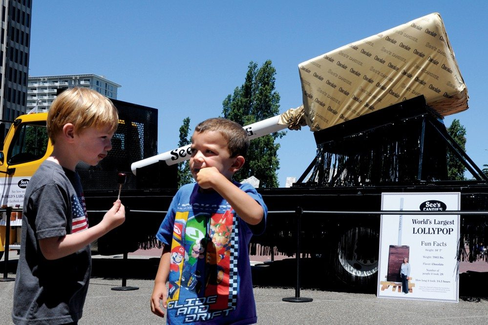 Beth Laberge/Special to the S.F. ExaminerSWEET!Oscar Craven-Green and Benjamin Maibrano eat a lollipop at the See's Candy lollipop giveaway in Justin Herman Plaza on Friday