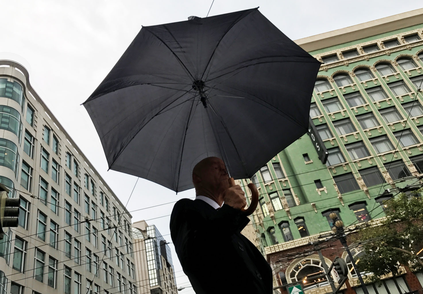 A man walks down Market Street as rain falls in San Francisco, Calif. August 4, 2017. (Jessica Christian/S.F. Examiner)