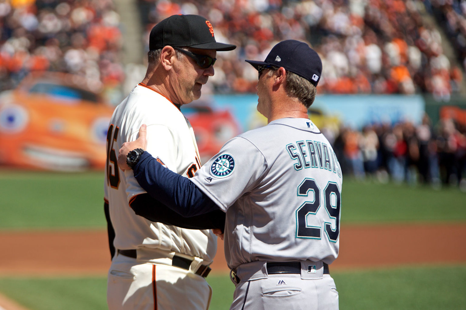 Bruce Bochy embraces Seattle Mariners manager Scott Servais, another MLB catcher-turned-manager, before the home opener at AT&T Park. (Kevin N. Hume/S.F. Examiner)