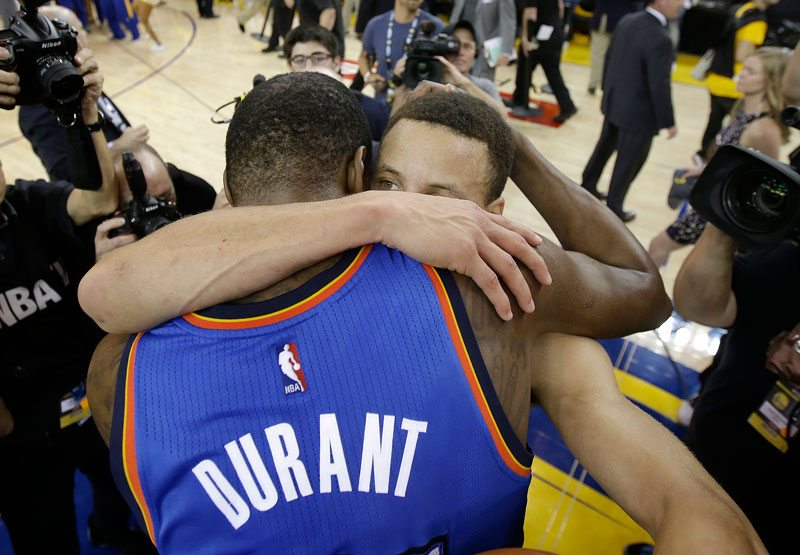 Oklahoma City Thunder forward Kevin Durant, foreground, hugs Stephen Curry after Game 7 of the NBA basketball Western Conference finals in Oakland, Monday, May 30, 2016. (Marcio Jose Sanchez/AP)