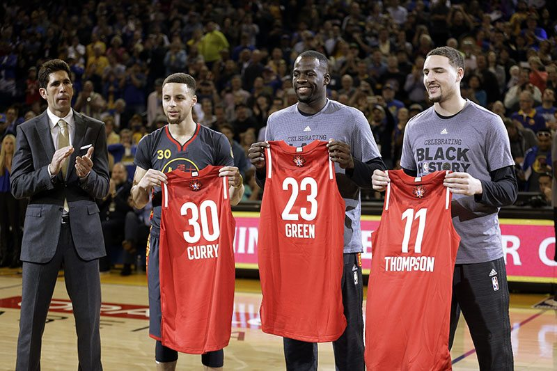 Golden State Warriors General Manager Bob Myers, left, applauds as Golden State Warriors' Stephen Curry (30) Draymond Green (23) and Klay Thompson (11) display their All Star Game jerseys prior to an NBA basketball game against the Houston Rockets on Tuesday, Feb. 9. (Ben Margot/AP)