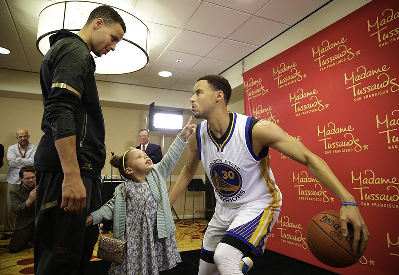 Golden State Warriors guard Stephen Curry, left, watches his daughter Riley as she examines his wax figure by Madame Tussauds after its unveiling on Thursday. The figure of the NBA MVP will go on display at Madame Tussauds wax museum at Fisherman's Wharf in San Francisco. (Eric Risberg/AP)