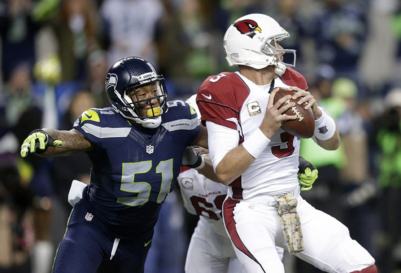 Seattle Seahawks outside linebacker Bruce Irvin (51) pressures Arizona Cardinals quarterback Carson Palmer during an NFL game in 2015. (Stephen Brashear/AP)