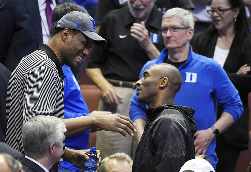 Former NBA player David Robinson, left, talks with Los Angeles Laker Kobe Bryant as Tim Cook, CEO of Apple looks on during the second half of an NCAA tournament game between Oregon and Duke in the regional semifinals on Thursday. (Mark J. Terrill/AP)