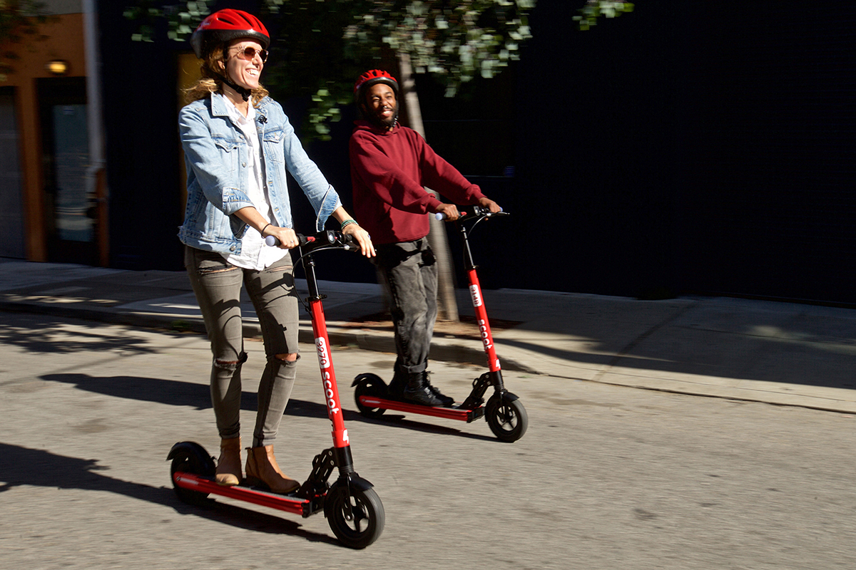 Scoot's Jasmine Wallsmith and Javon Salone ride the company's new Kick scooter on Tuesday, Oct. 9, 2018 ahead of The City's rollout of permitted scooters. (Kevin N. Hume/S.F. Examiner)