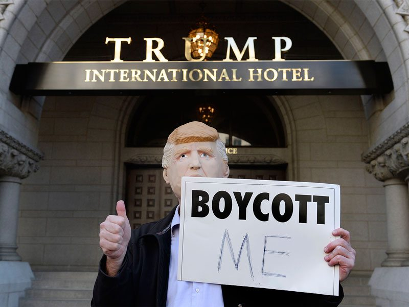 A demonstrator stands outside Trump International Hotel Washington during its grand opening on Wednesday in Washington, D.C. (Olivier Douliery/Abaca Press/TNS)