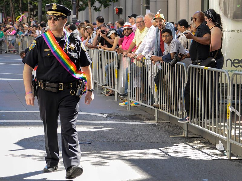 A San Francisco police officer walks down Market Street wearing a rainbow-colored sash while patrolling the Pride Parade. (Jessica Christian/S.F. Examiner file photo)