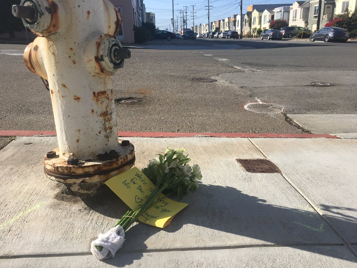 """Flowers at the scene of a homicide at 46th Avenue and Moraga Street. """"We're sorry for the end of your life — Neighborhood family."""" Neighbors say they heard multiple gunshots. (Michael Barba/S.F. Examiner)"""