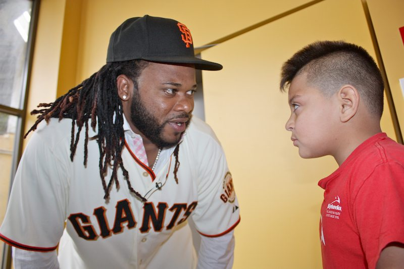 Newly acquired Giant Johnny Cueto takes an extra moment to talk baseball with  second grader, Dannis Salazar, who missed out on the school Q&A. The Giants organization plan to have Salazar specially attend a game when Cueto is pitching (Kevin Kelleher/Special to S.F. Examiner)