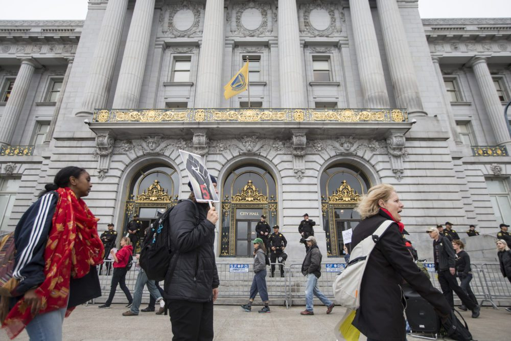 Demonstrators hold signs while marching in a circle during a general strike in front of City Hall in San Francisco, Calif. Monday, May 9, 2016 in support of the five San Francisco residents who ended their seventeen day hunger strike calling for the resignation or firing of SFPD Chief Greg Suhr. (Jessica Christian/S.F. Examiner)