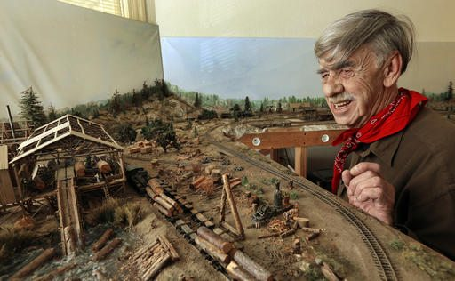 In this photo taken on Wednesday, March 16, 2016, Charles Edwards looks over his model train layout in Alameda. (AP Photo/Ben Margot)