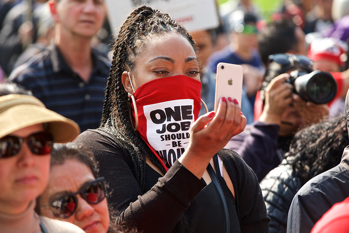 A striking Marriott hotel worker with UNITE HERE Local 2 records a speaker at a rally at Yerba Buena Gardens on day 40 of the strike on Monday, Nov. 12, 2018. (Kevin N. Hume/S.F. Examiner)