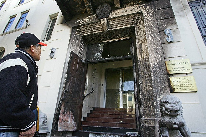 Mike Koozmin/The S.F. ExaminerA man looks at the burned out doorway of the Chinese Consulate Thursday morning. Federal officials are leading an arson investigation while consulate workers say surveillance footage showed a person pouring the contents of two buckets on the front of the building and setting it on fire.