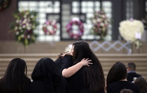 Friends of Yvette Velasco embrace as they arrive for a memorial services, Thursday, Dec. 10, 2015 in Covina, Calif. Velasco died in a mass shooting Wednesday, Dec. 2, in San Bernardino, Calif. (AP Photo/Jae C. Hong)