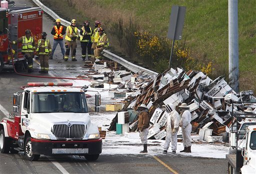 Mark Mulligan /The Herald via APBeekeepers along with firefighters and WSDOT workers attempt to clear the freeway of bee hives that spilled off of a semitruck along northbound Interstate 5 on Friday