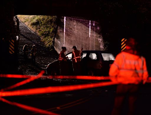 Emergency personnel, including South Carolina Highway Patrol and the Spartanburg County Coroner's Office, work on the scene where several cars were trapped briefly under a bridge during flooding from heavy rain Thursday morning. (AP Photo/Spartanburg Herald-Journal/Tim Kimzey)