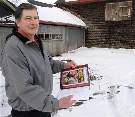 """Walter Yacoboski holds an auction guide featuring one of his comic books, """"Amazing Fantasy"""" No. 15, which features the Spider-Man character. (AP Photo/Frank Eltman)."""